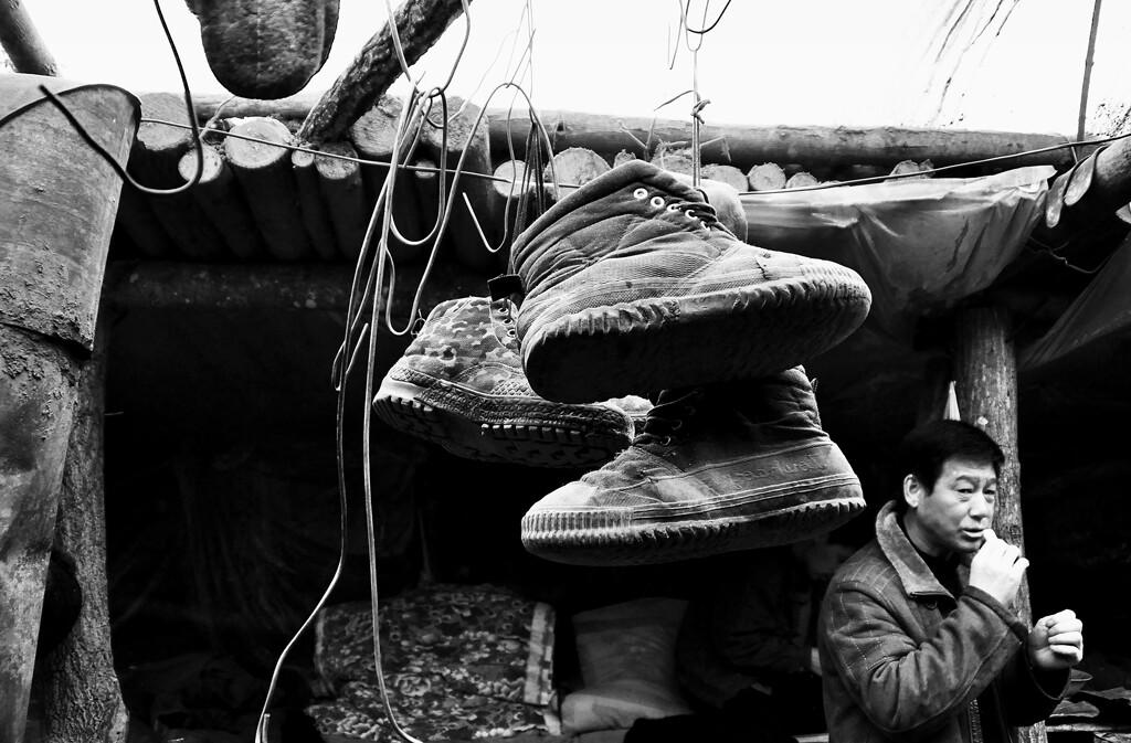 摄影 山里/16 棚子上面有许多的钩子,是钩鞋子用的,每天下班了工人们把鞋...